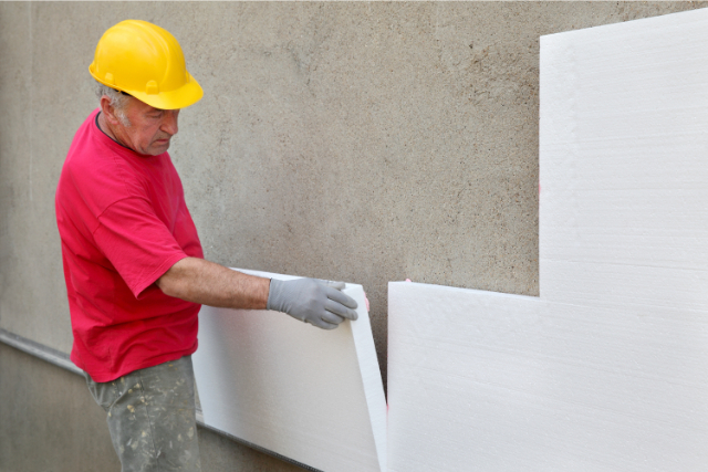 Thermal Wall insulation by worker with a yellow hard hat on.
