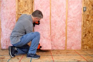 Worker installing fiberglass insulation in a home.